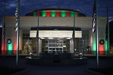 Flags sit at half mast as the sun rises behind The George Bush Library and Museum, that is lit for Christmas a day after the 41st president of the United States died, in College Station