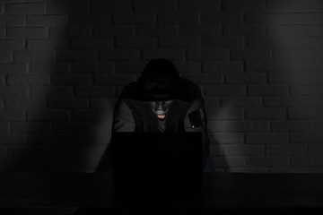 Hacker in black mask and hood at the table