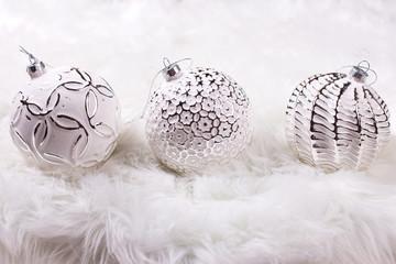 Three white balls on white fur background.