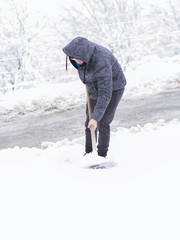 Young man cleaning snow at backyard. Cold snowy winter day.
