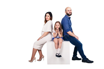 Happy young family sitting on a pedestal against white background.
