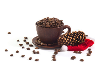 A cup with coffee beans and a New Year hat at the white background