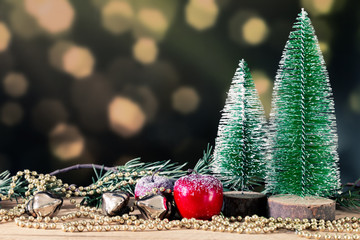 Christmas decoration green background with fir trees golden perls and red apple