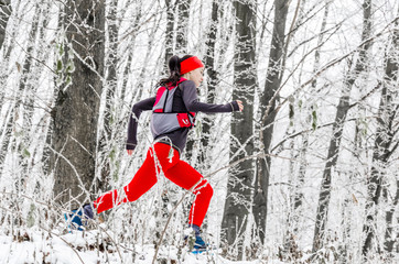Young woman athlete in red leggings runs in the winter forest. Side view. Winter sports. Extreme running.