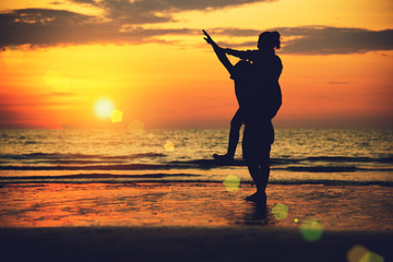 Asian lovers happy on the beach with a beautiful sunset in background man lifting the woman. Travel  relax on the beach vacation. in summer