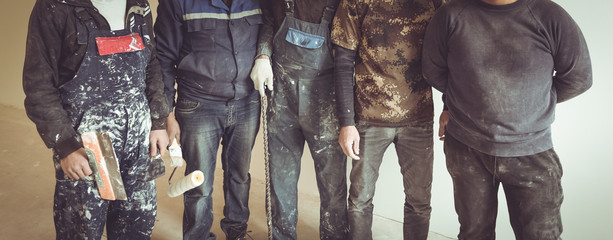 Workers and builders and  foreman are as gang with dirty uniform are staying in apartment that is under construction, remodeling,renovation,extension, restoration, overhaul and reconstruction