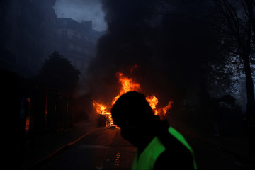 A protester wearing a yellow vest, a symbol of a French drivers' protest against higher diesel taxes, stands near a burning car during clashes near the Place de l'Etoile in Paris