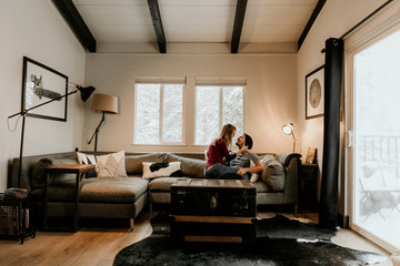 Young Attractive Caucasian Loving Valentines Couple Cuddling on Sectional Couch Furniture in Trendy Modern Minimalist Designed Living Room Black and White Interior