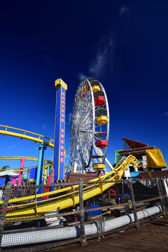 Ferris wheel and roller coaster tracks in the amusment park on Santa Monica Pier in os Angeles, California