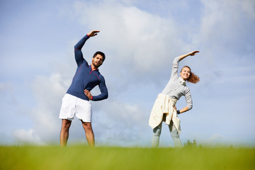 Happy young active couple in sportswear exercising on green grass on summer weekend