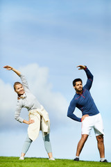 Young couple in activewear side-bending in natural environment on sunny morning
