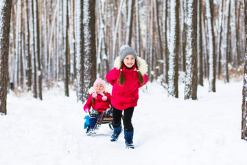 little girls playing on winter winter holidays in a winter forest