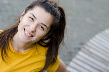 Pale brunette girl in yellow t-shirt walking around the city and posing for photo with inspired face expression. Active young woman in casual summer outfit having fun.