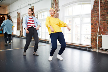 Two young active women doing hip hop exercises on the floor with large mirror on background
