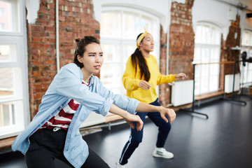 Young active woman and her groupmate learning hip hop dancing in modern studio