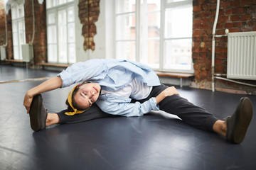 Young active female doing stretching exercise for arms and legs while sitting on the floor in studio
