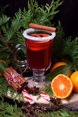 Hot mulled wine with slices of citrus fruits, cinnamon and anise in an Irish glass decorated with sugar border