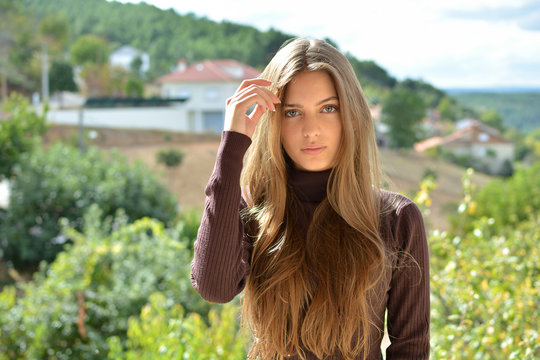 portrait of a beautiful ,healthy and attractive young woman with long hair and beautiful face with outdoor background