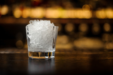 Elegant low cocktail glass filled with ice cubes on the bar counter of restaurant