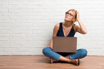 Blonde girl sitting on the floor with her laptop standing and thinking an idea on white brick wall background
