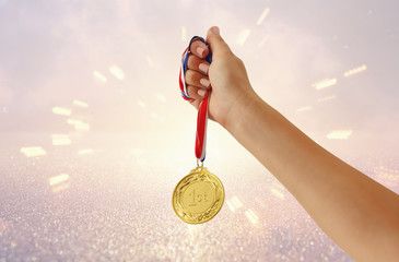 woman hand raised, holding gold medal against glitter background. award and victory concept.
