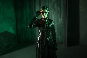 Girl hacker in the digital world. Young woman in matrix style suit.
