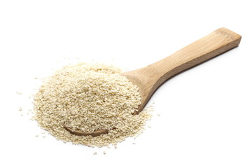 Pile sesame seeds and wooden spoon isolated on white