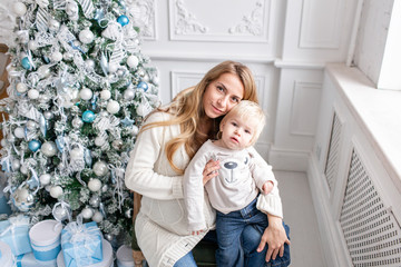 Happy family Portrait In Home - young pregnant mother embraces his little son. Happy new year. decorated Christmas tree. Christmas morning in bright living room.