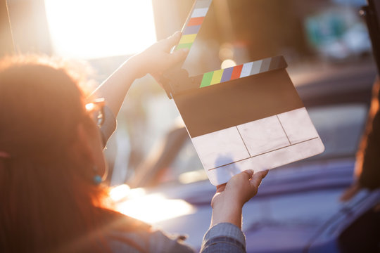 Filming on location. Woman holding a clapperboard in front of the camera, the filming process.