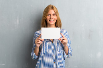 Blonde girl holding an empty placard on textured grunge wall background