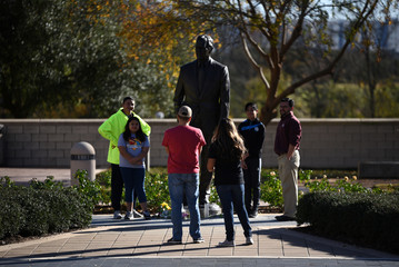 People pose for photos outside George H.W. Bush Presidential Library and Museum, a day after the 41st President of the United States died, in College Station