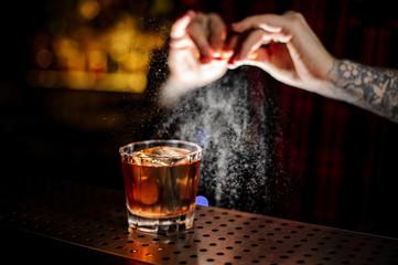 Aluminium Prints Cocktail Tattooed barman sprinkling orange peek juice into cocktail glass with whiskey