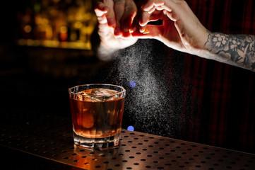 Aluminium Prints Cocktail Tattooed bartender sprinkling orange peek juice into cocktail glass with whiskey