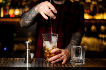 Barman stirring strong whiskey cocktail with ice cubes