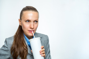 Business girl in a suit drinking soda water