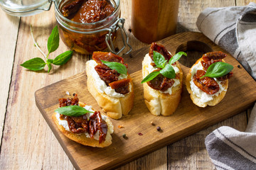 Italian Antipasti snacks for Wine. Brushetta with Soft Cheese and Dried Tomatoes on a wooden table.