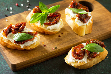 Antipasti snacks for Wine. Brushetta with Soft Cheese and Dried Tomatoes served on a rustic wooden board on a stone table.