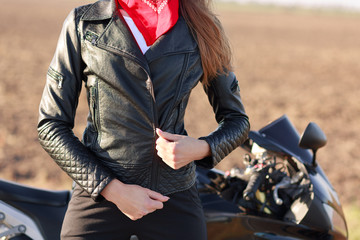 Cropped image of sporty woman zips her black leather jacket, prepares for racing competiotns or marathon, poses near motorbike, enjoys extreme sport. People, hobby and transportation concept