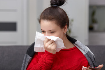 Close up shot of ill woman sneezes and has running nose, wrapped in coverlet, holds mobile phone and tissue, has hair knot, poses against blurred domestic background. Health problems concept