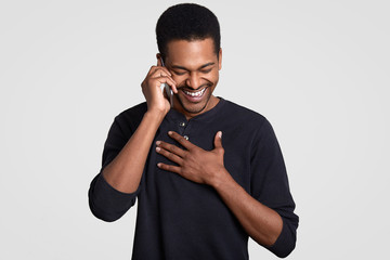 Funny joyful dark skinned masculine laughs happily, hears comic story from friend on cell phone, keeps hands on chest, giggles positively, isolated over white background. Positive emotions concept