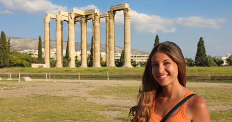 Smiling tourist woman with the greek temple of Olympian Zeus on the background, Athens, Greece. Panoramic banner crop..