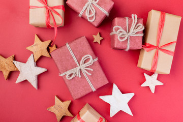 Christmas composition. Christmas red decorations, stars and gift boxes on red background. Flat lay, top view, space for the text