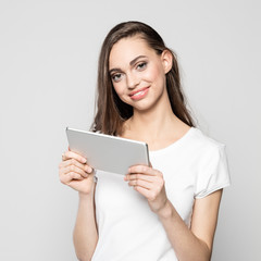 Portrait of friendly young woman holding digital tablet