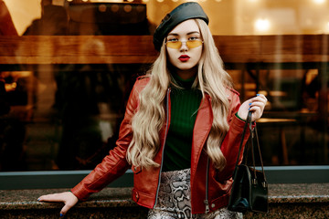 Outdoor fashion portrait of young woman wearing red biker jacket, trendy orange sunglasses, leather beret, snake skin print trousers, holding bag, posing in street of city. Copy, empty space for text