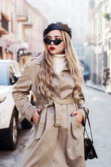 Outdoor fashion portrait of young beautiful fashionable lady with long blond hair, wearing trendy beige long trench coat, stylish cat eye sunglasses, leather beret, posing in street of european city