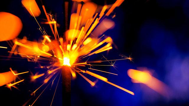 Sparkler Over Violet. Gun powder sparks shot against deep dark background. Burning fuse or bengal fire Isolated. Mojo-style coloring. Lightening Christmas sparkler