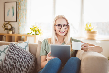 Young woman resting on sofa with coffee and digital tablet