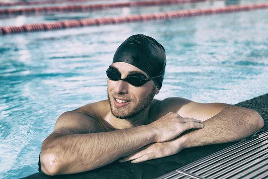 Swim athlete man wearing sport glasses and cap in indoor swimming pool.