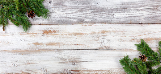 Christmas Evergreen decorations in left and right corners on white vintage wooden boards