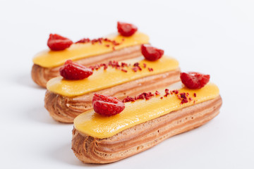 Set of delicious eclairs with yellow glaze and raspberries